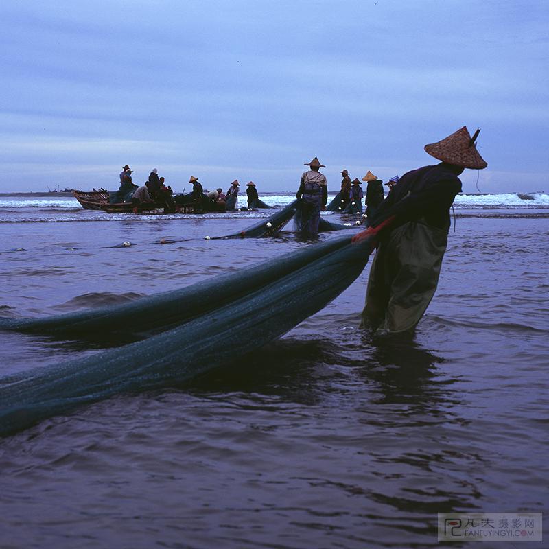 渔船撒网归来,岸上渔民准备收网